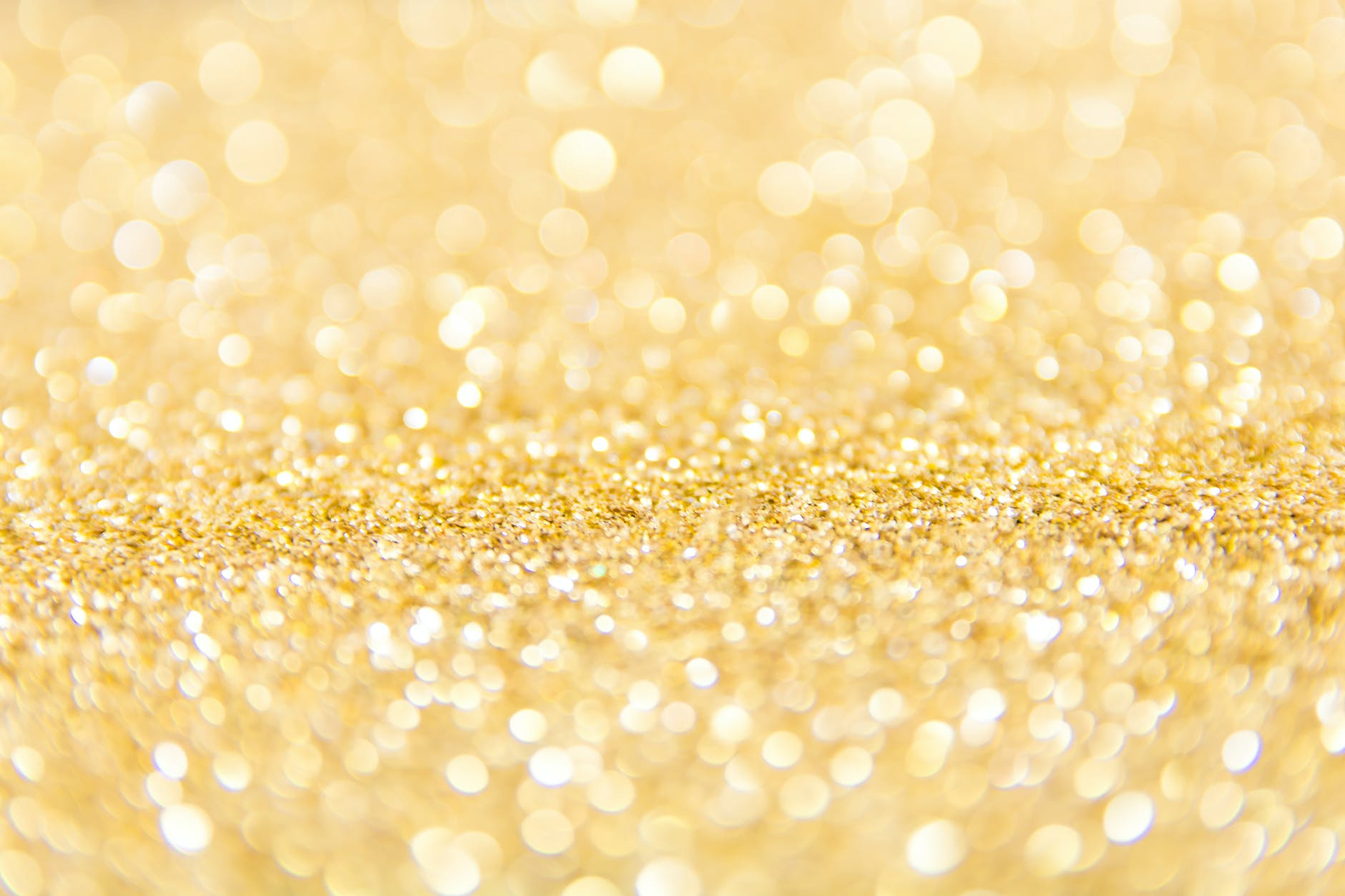 A gold sparkly glitter spread over a surface.